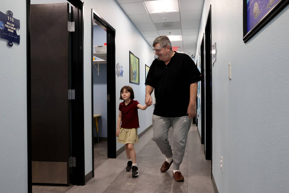 Akara Haase, 6, leaves with her father Gary Haase after a session at the Center for Autism and ...