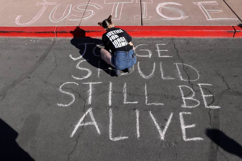 Jazz Appin writes messages in chalk on the ground outside the Clark County Government Center on ...