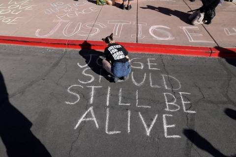 Jazz Appin of Las Vegas writes on the ground outside the Clark County Government Center in Las ...
