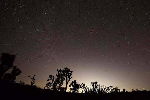 Las Vegas glows in the distance as a meteor streaks above the Mojave Desert before dawn in 2018 ...