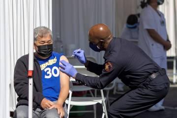 A man receives a COVID-19 vaccine shot at the Tiburcio Vasquez Health Center's vaccination site ...