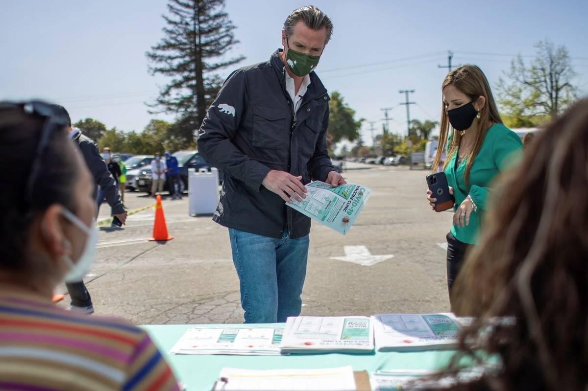 California Gov. Gavin Newsom, left, grabs a flyer as Tiburcio Vasquez Health Center CEO Andrea ...