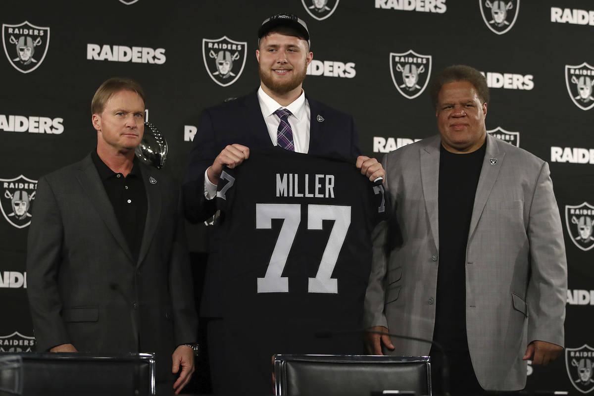 Oakland Raiders draft pick Kolton Miller stands between coach Jon Gruden, left, and General Man ...