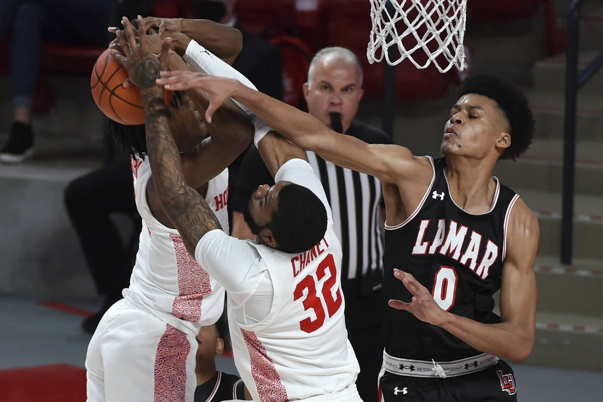 Lamar center David Muoka (0), Houston forward Reggie Chaney (32), and guard Tramon Mark, left, ...