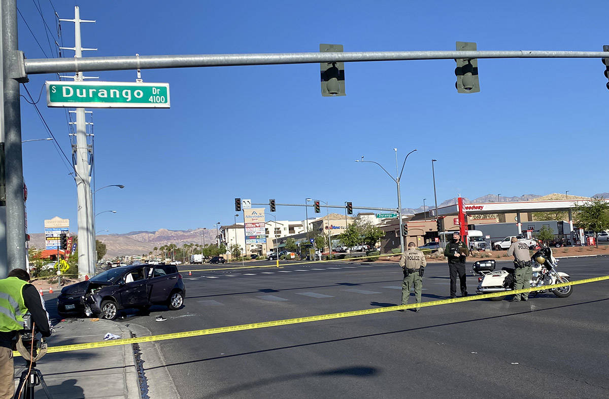 Las Vegas police officers at the scene of an SUV that crashed into a power line transmission po ...