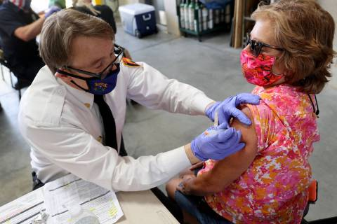 Clark County Fire Department Chief John Steinbeck gives a COVID-19 vaccine to Lynn Mendez, 58, ...