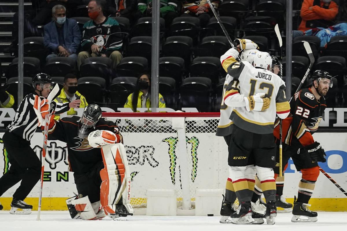 Vegas Golden Knights players celebrate and Anaheim Ducks goaltender John Gibson, left, kneels a ...