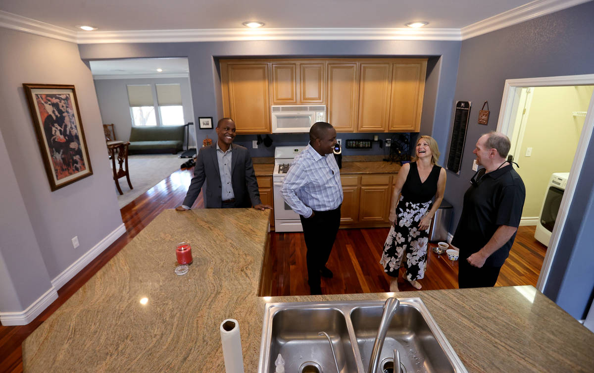 Realtor Shawn Cunningham, second from left, and his brother Kyle Cunningham, left, show a Las V ...