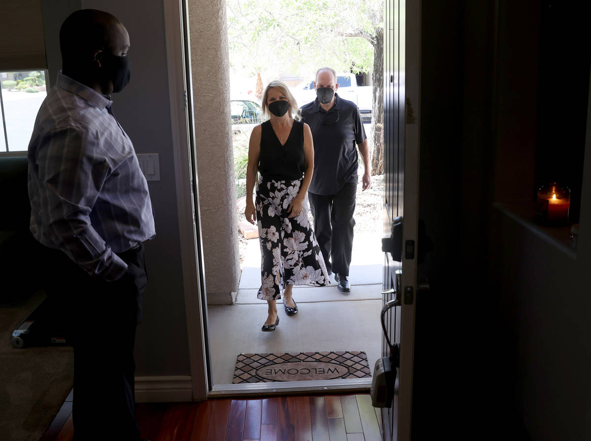 Realtor Shawn Cunningham, right, shows a Las Vegas house for sale to David Verno and Trudy Lope ...