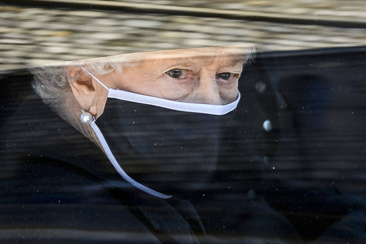 Britain's Queen Elizabeth II follows the coffin in a car as it makes it's way past the Round To ...