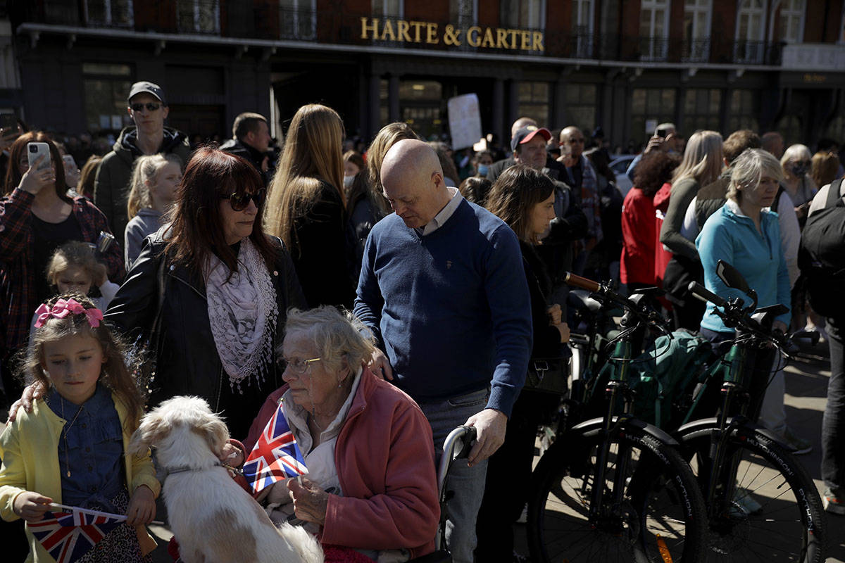 People observe a minute's silence outside Windsor Castle during the funeral of Britain's Prince ...