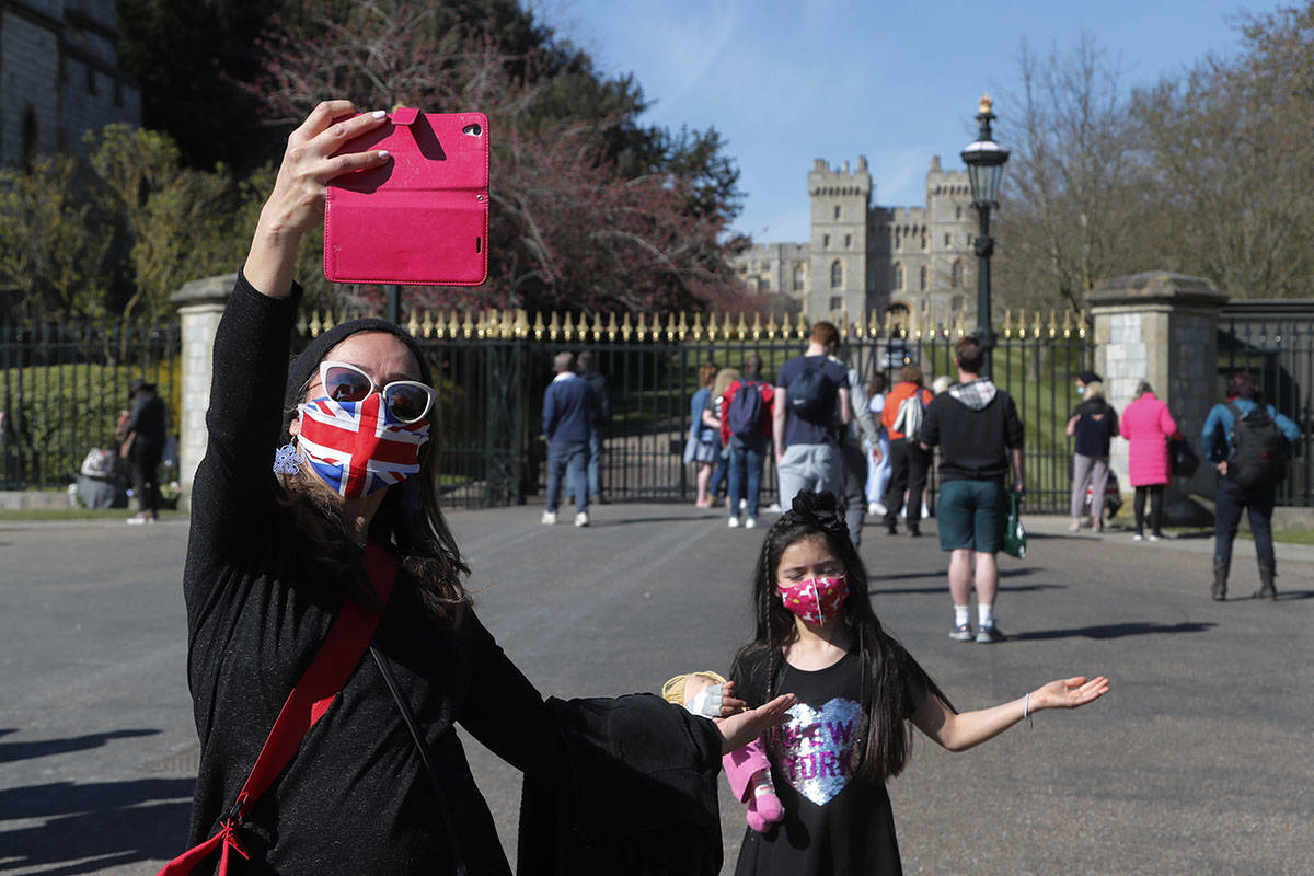 People take photographs outside the Windsor Castle in Windsor, England, following the funeral o ...