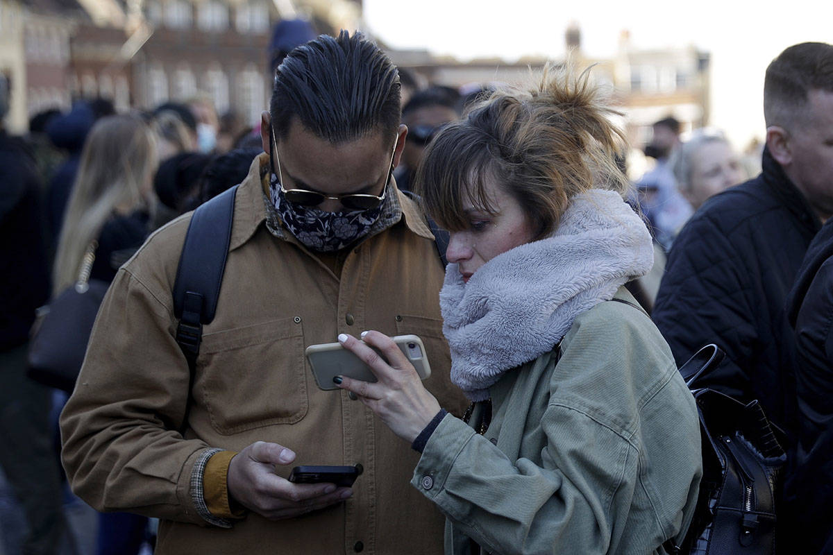 People watch live coverage on a phone outside Windsor Castle during the funeral of Britain's Pr ...