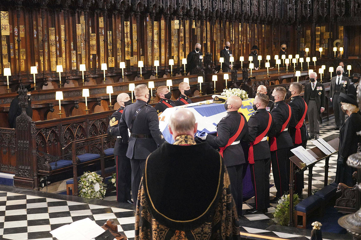 Britain's Queen Elizabeth II, obscured left, looks on the flag draped coffin in St. George&#x20 ...