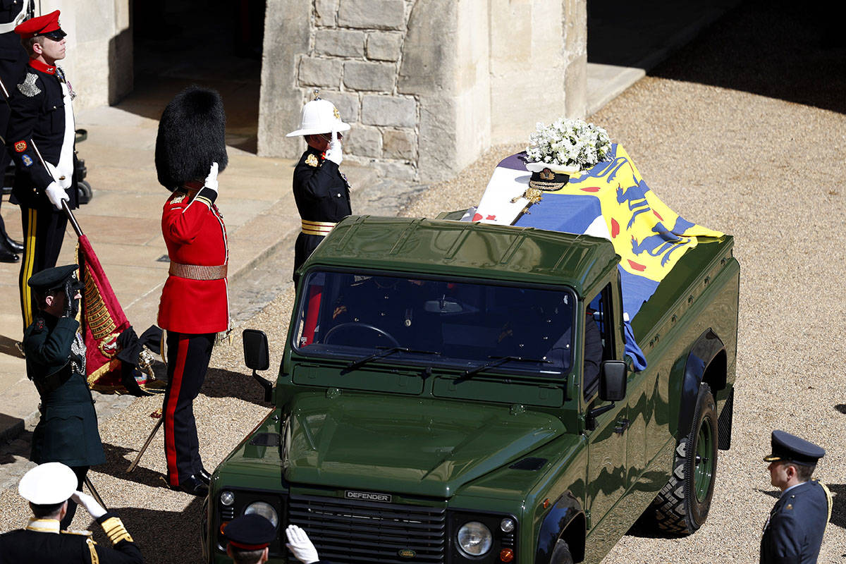 Members of the military salute the coffin of Britain's Prince Philip as it sits atop a modified ...