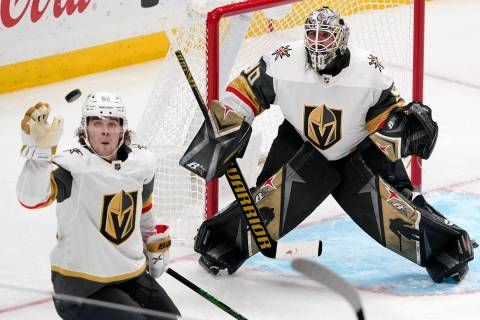 Vegas Golden Knights defenseman Dylan Coghlan, left knocks the puck out of the air as goaltende ...