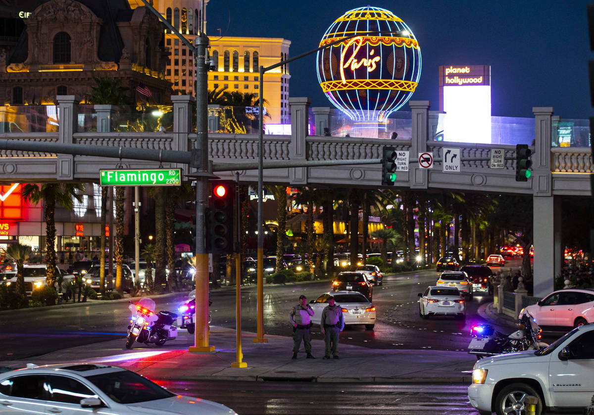 Las Vegas police watch from a distance as people participate in a demonstration in solidarity w ...