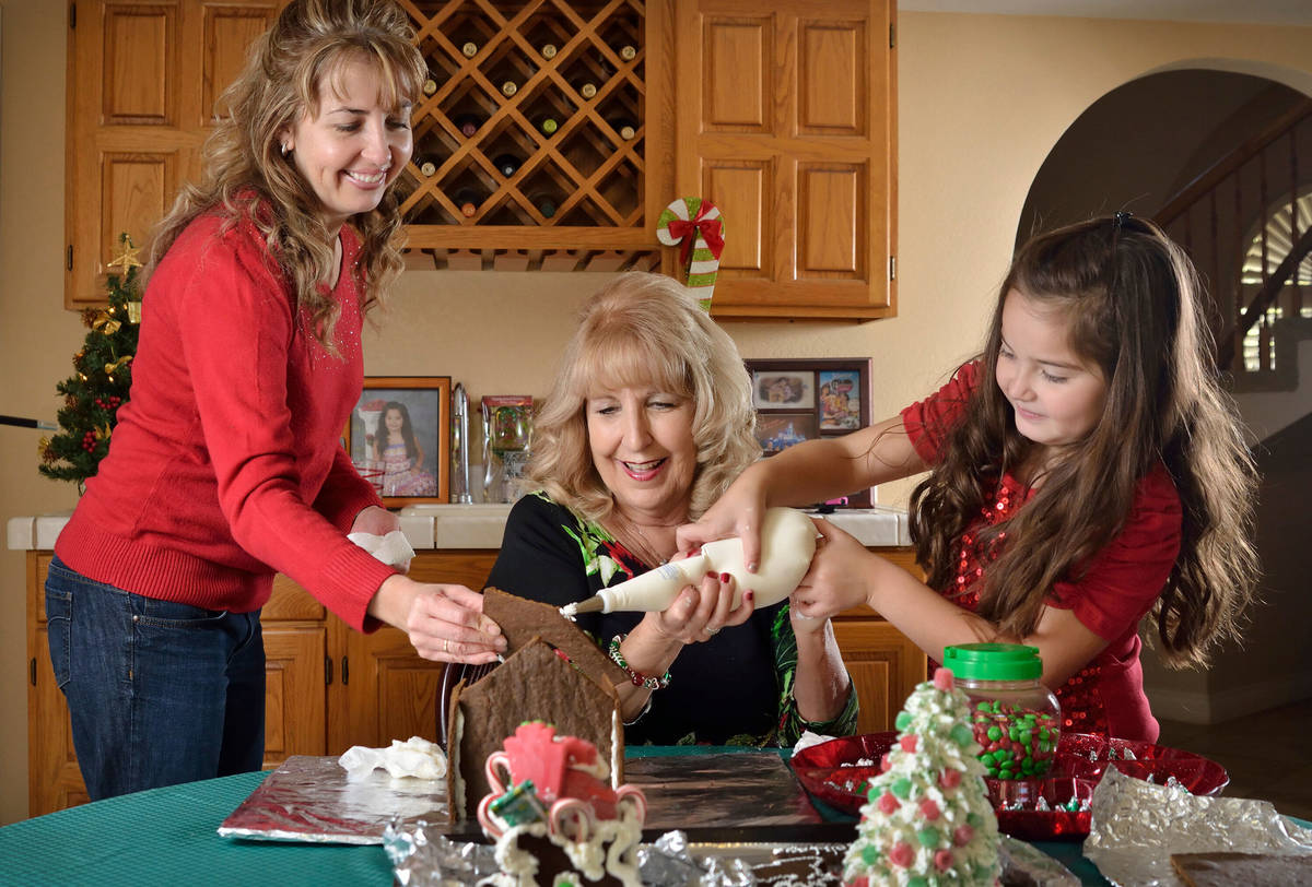Judy DuCharme, center, works on a gingerbread house with her daughter Desiree Romero, left, and ...