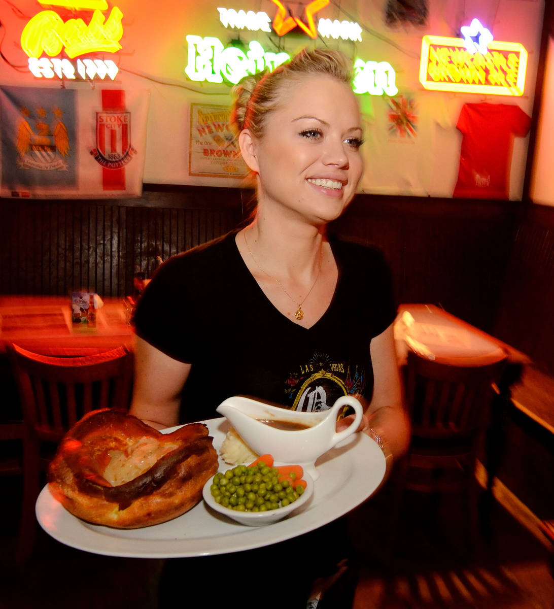Christina Jones serves up an English dish known as a Toad in the Hole at the Queen Victoria Pub ...