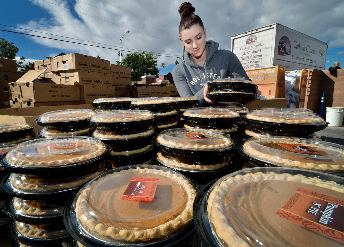 Volunteer Kaylei Dunn stacks pumpkin pies during a Thanksgiving food giveaway at Catholic Chari ...