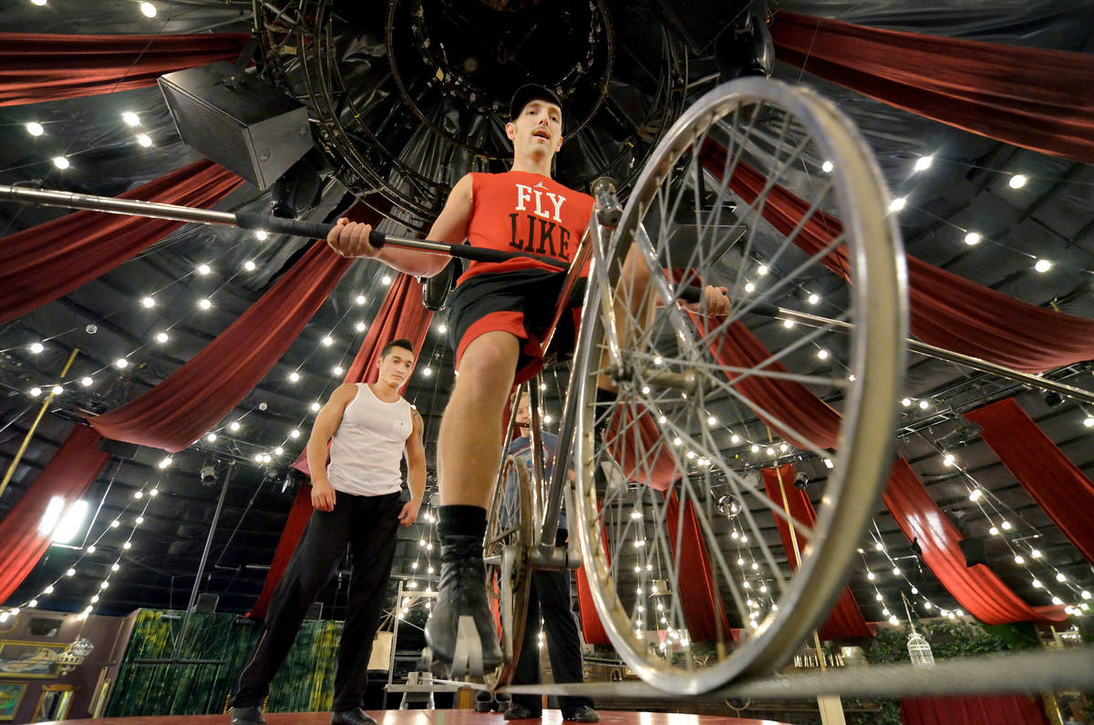 "Tony Hernandez rides a bike on the wire while Almas Meirmanov looks on during a rehearsal for "" ..."