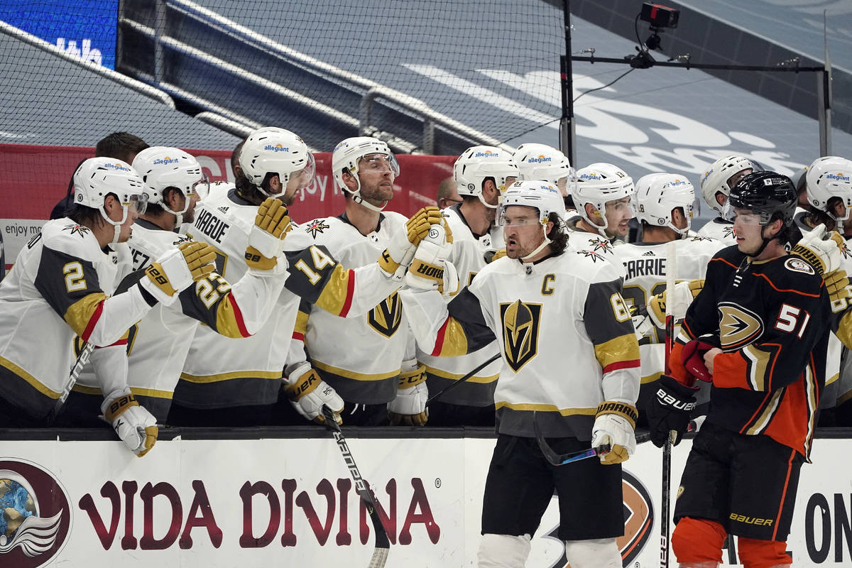Vegas Golden Knights right wing Mark Stone, center right, high-fives teammates on the bench aft ...