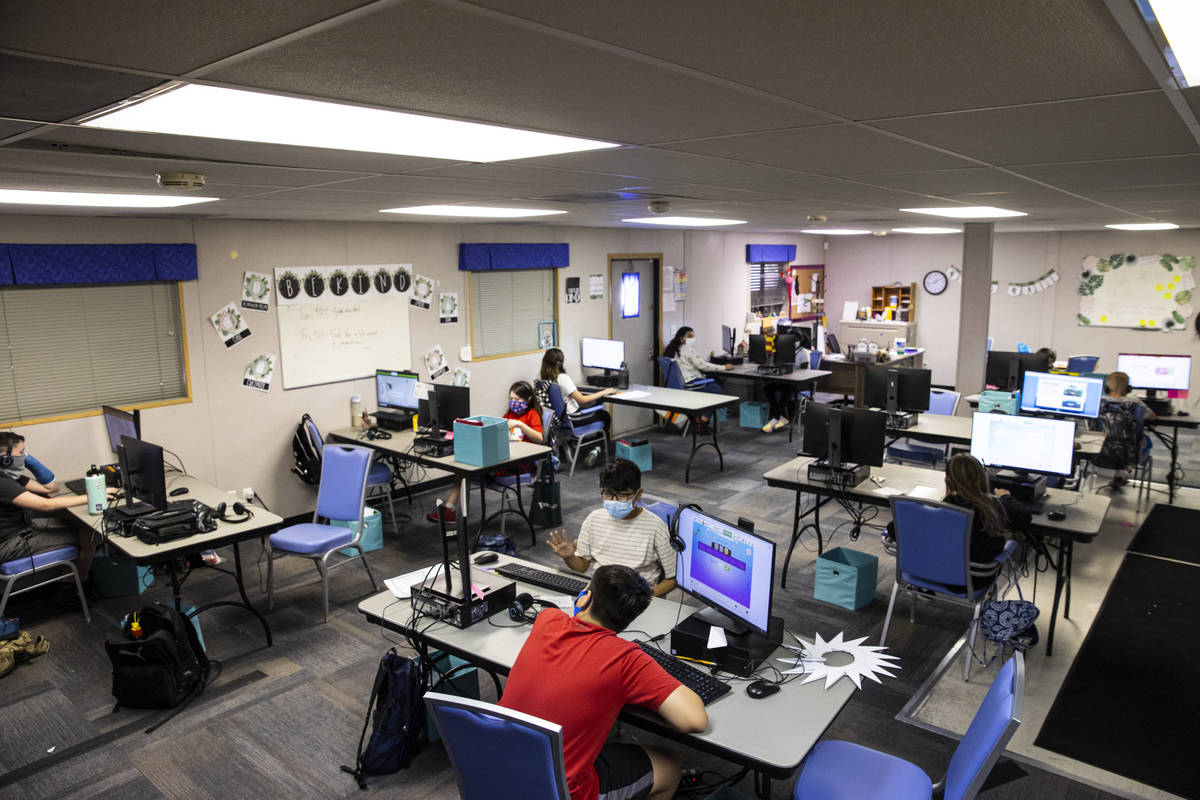 Fifth-graders Michael Bean, center, in red, and Aaron Falcon, in white, work on math studies du ...
