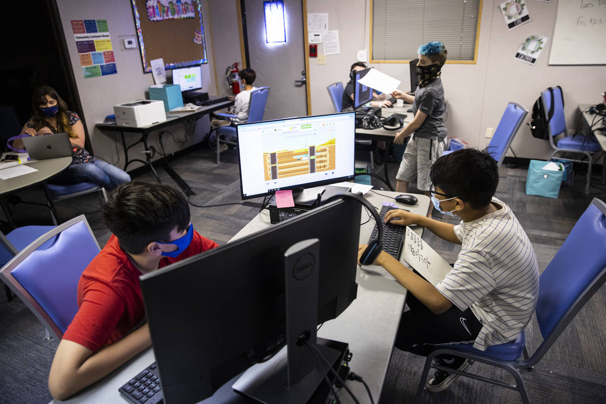 Fifth-graders Michael Bean, left, and Aaron Falcon, both 11, work on math studies during a clas ...