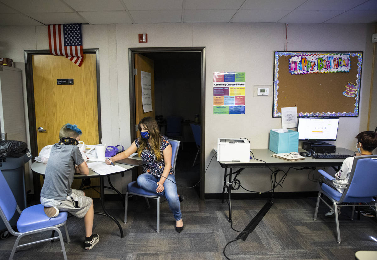 Ashley Campbell, chief of staff at Nevada Action, second from left, helps fifth-grader Jack Gri ...
