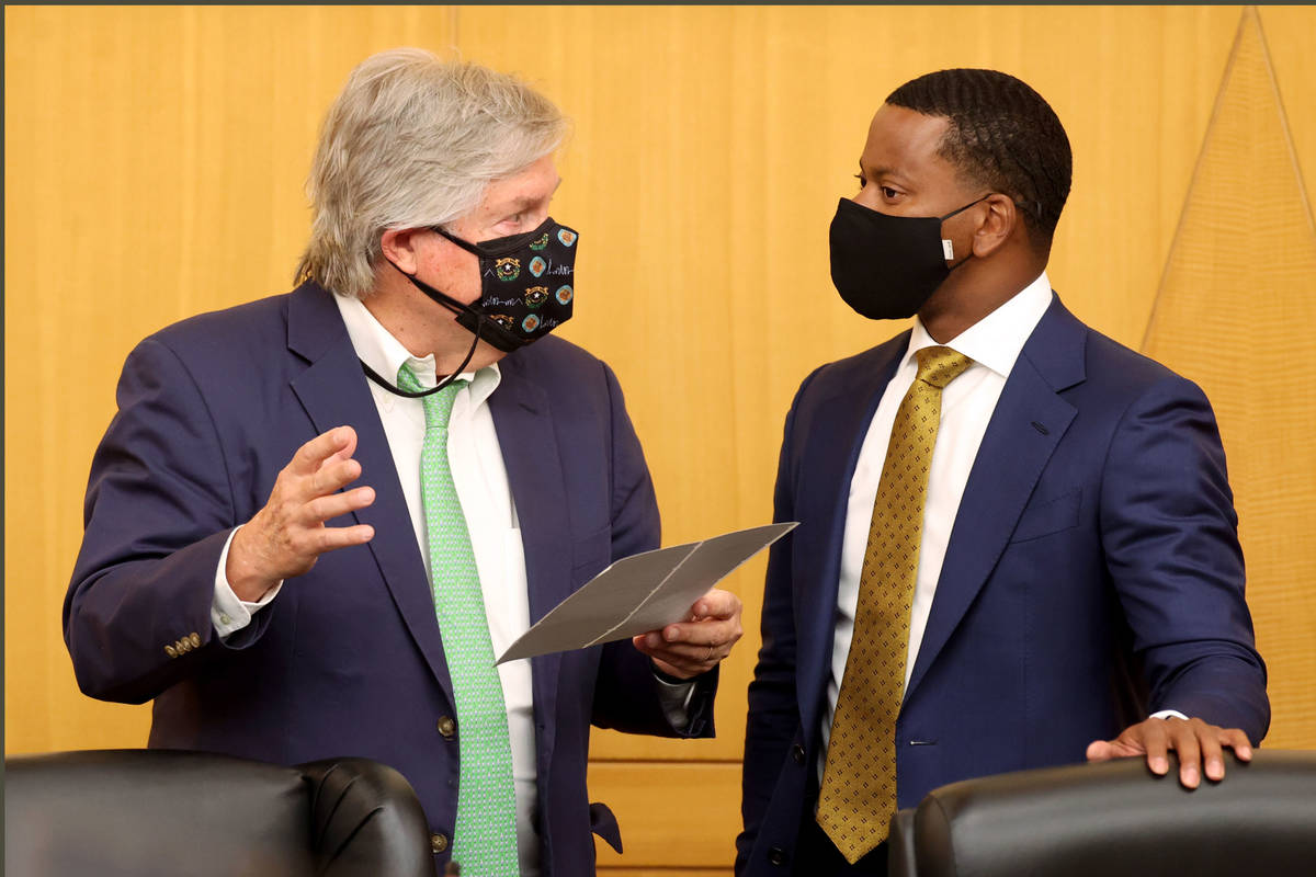Clark County commissioners Tick Segerblom, left, and William McCurdy II talk before a commissio ...