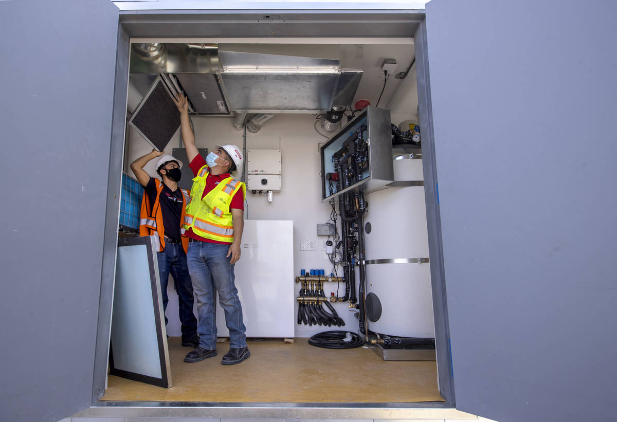 Students Alejandro Munoz, right, and Miguel Vazquez look at the ventilation system as a UNLV te ...