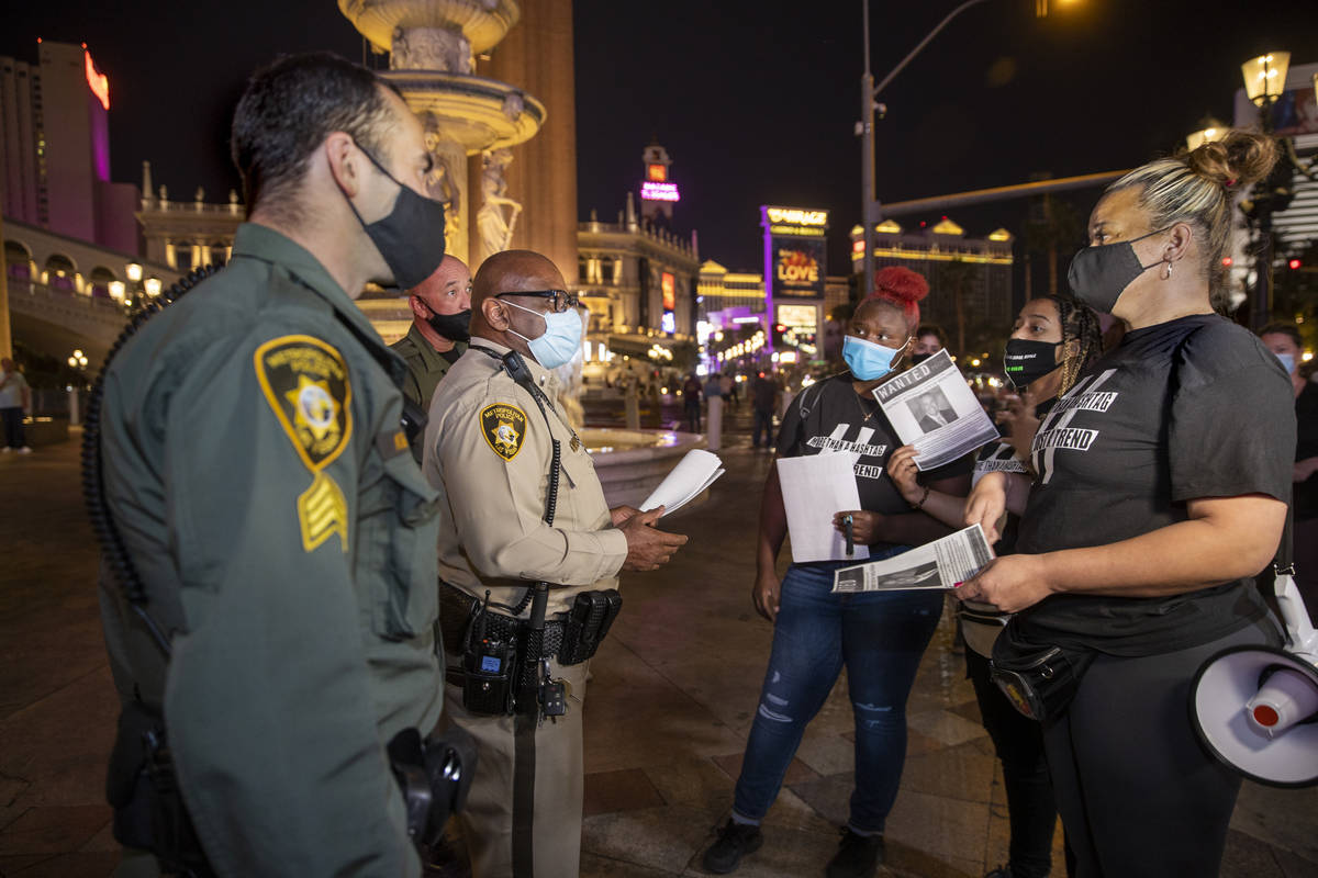 Las Vegas police make contact with organizers before they leave the Venetian to march along the ...