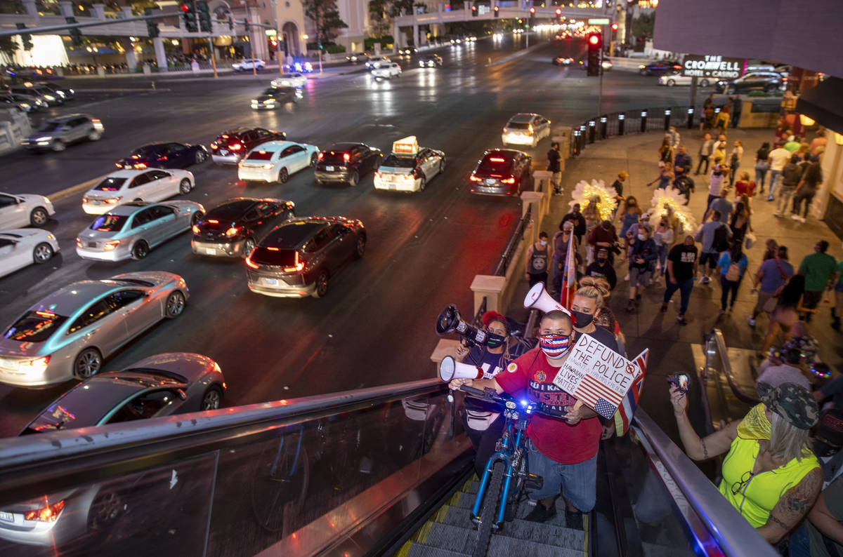 A small group heads up to a pedestrian bridge during a march along the Strip following the conv ...