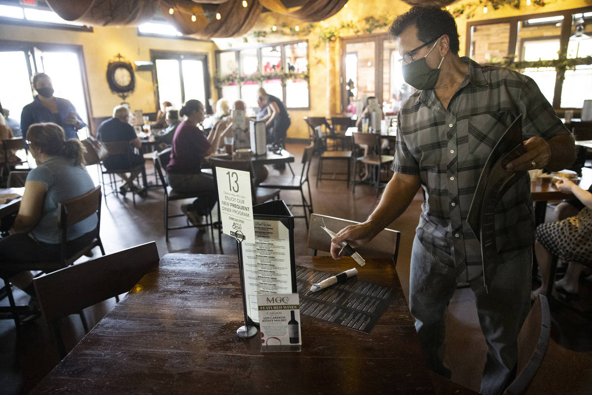 Joe Pierro, owner of Market Grille Cafe, sets up a table for customers. Labor shortages are req ...