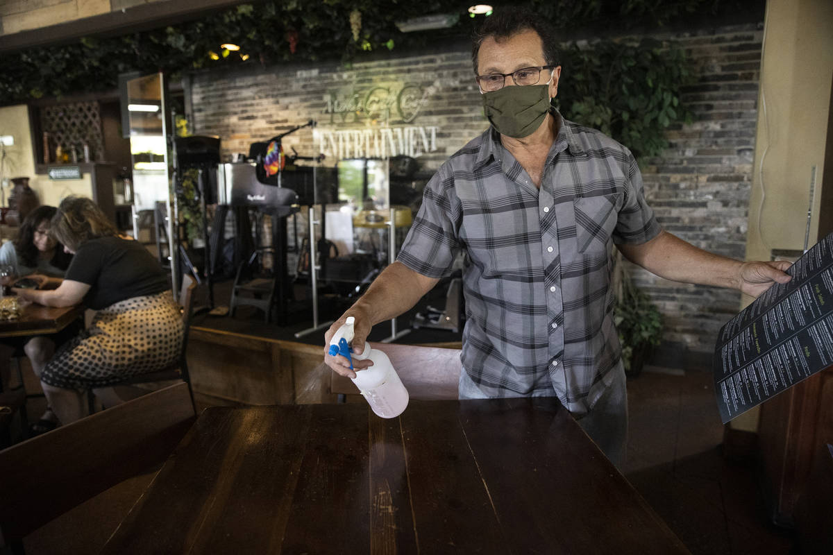 Joe Pierro, owner of Market Grille Cafe, cleans a table before seating customers. Despite offer ...