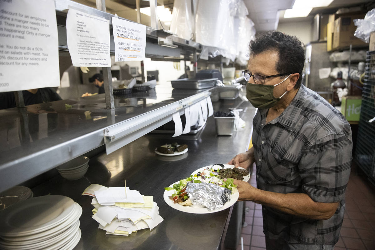 Joe Pierro, owner of Market Grille Cafe, runs food to customers at his restaurant because he is ...