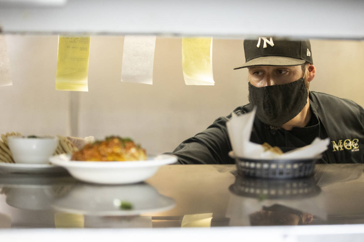 Joe Pierro Jr., the son of Market Grille Cafe owner Joe Pierro, sends out an order during lunch ...