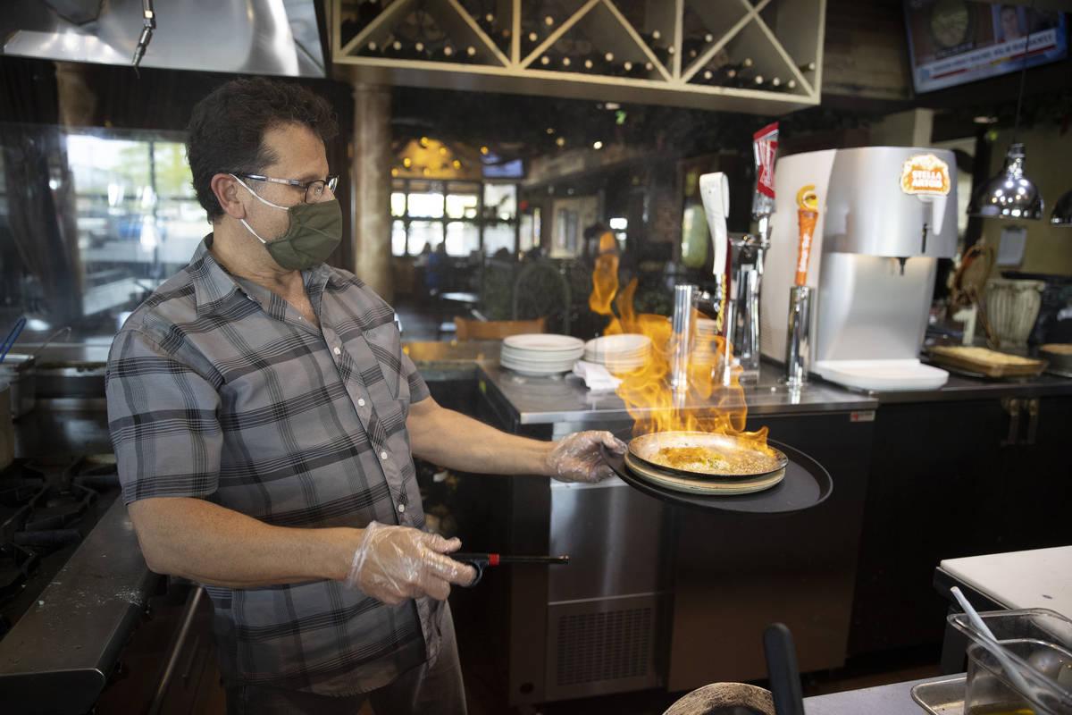 Joe Pierro, owner of Market Grille Cafe, prepares Saganaki at his restaurant. (Erik Verduzco/La ...