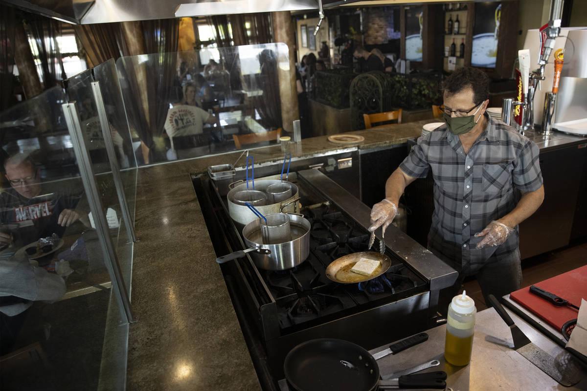 Joe Pierro, owner of Market Grille Cafe, prepares Saganaki at his N. Durango Drive restaurant. ...