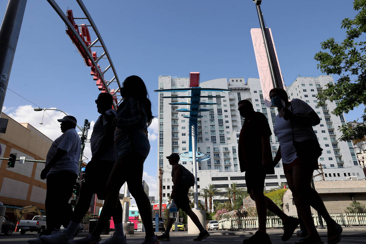People walk on Fremont Street at Las Vegas Boulevard downtown Wednesday, April 21, 2021. (K.M. ...