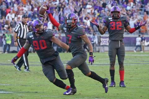 TCU safety Trevon Moehrig (7) celebrates his interception with teammates Ross Blacklock (90) an ...