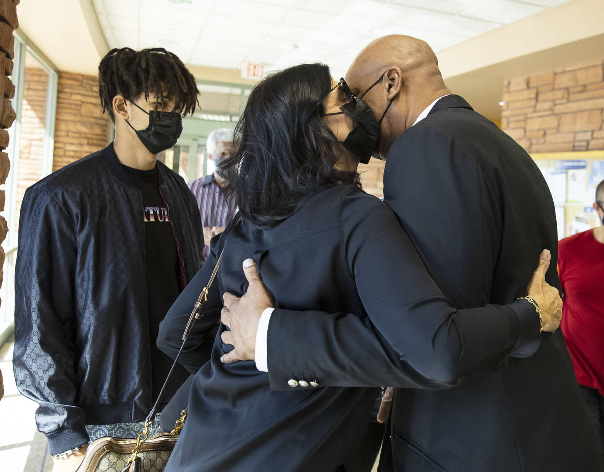 Former NBA player Jackie Robinson embraced by his wife Maria as their son J.J. looks on after t ...
