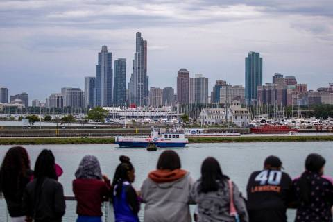 A group of people stand along Lake Michigan as they view Chicago's skyline from Navy Pier, Frid ...