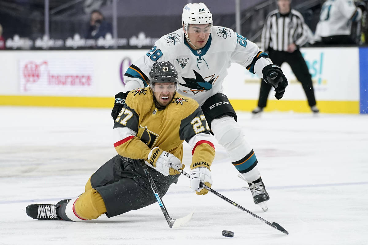 Vegas Golden Knights defenseman Shea Theodore (27) vies for the puck with San Jose Sharks right ...