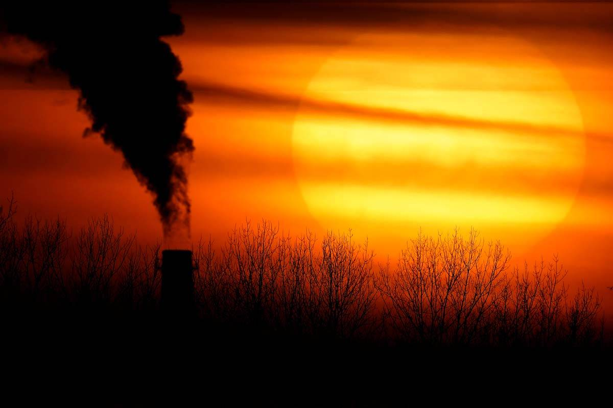 In this Feb. 1, 2021 file photo, emissions from a coal-fired power plant are silhouetted agains ...