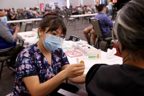 Deanna Chea of UNLV Medicine gives a COVID-19 shot at the UNLV vaccination site Monday, April 5 ...