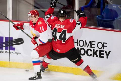 WHL player Bowen Byram fights for control of the puck with Russia's Maxim Marushev during secon ...