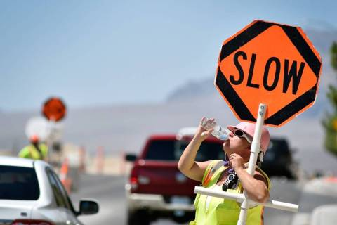 Flagger Shayne Boley guides vehicles though a construction zone on North Grand Canyon Drive in ...