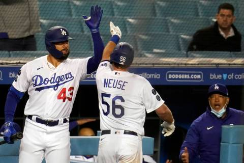 Los Angeles Dodgers' Sheldon Neuse (56) celebrates his solo home run with Edwin Rios (43) durin ...