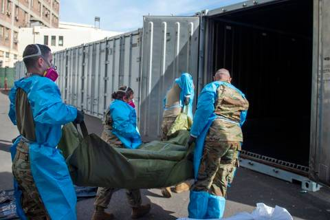 National Guard members, assisting with processing COVID-19 deaths, place bodies into temporary ...